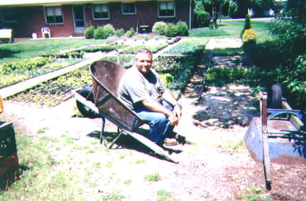Mike McGroarty sitting in a Jackson wheelbarrow